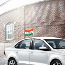 indian flag mounted on cars window with a plastic staff