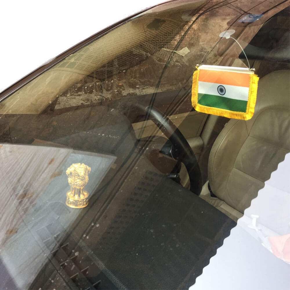 indian flag kept below cars rear view mirror on the windshield with vacuum base