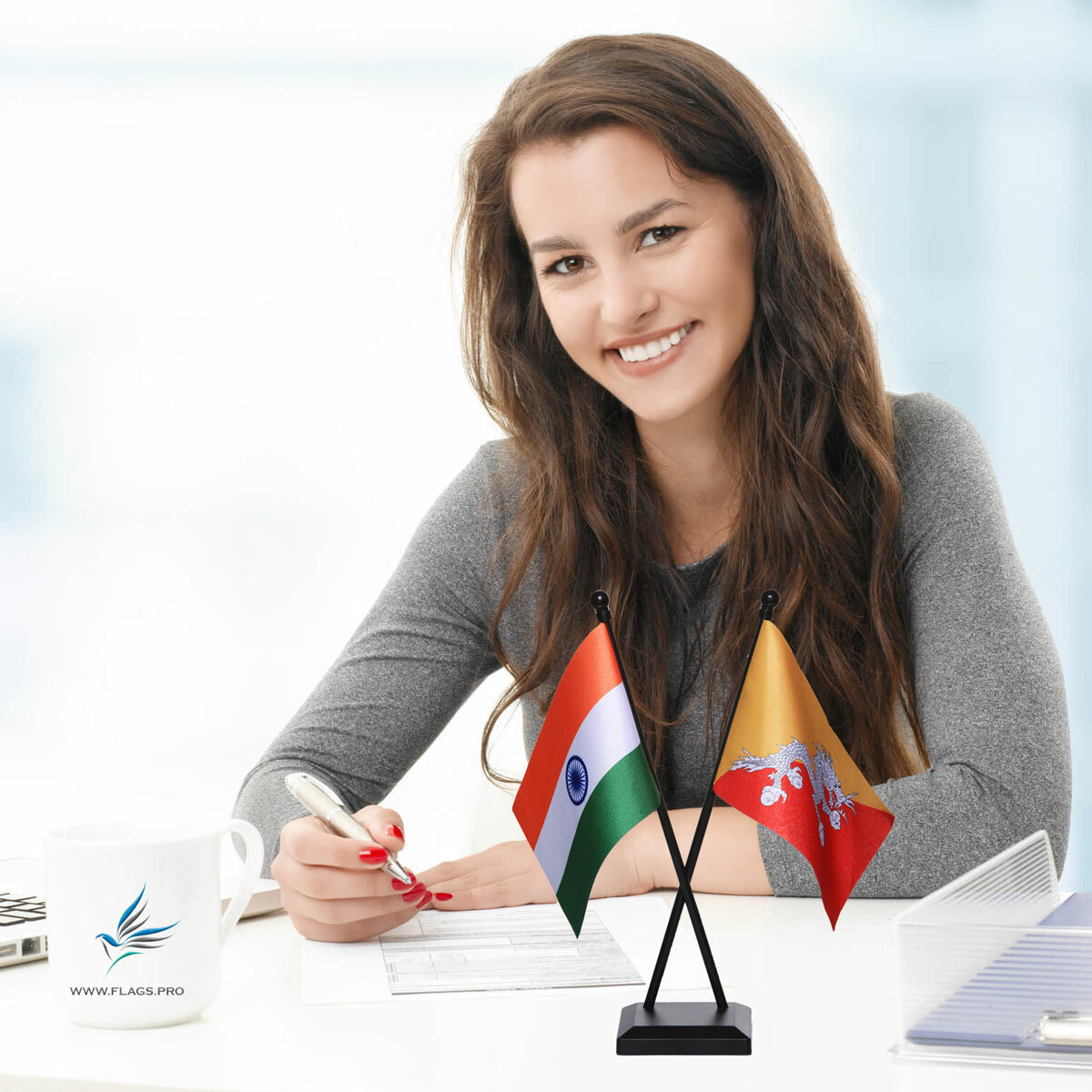 girl sitting at office desk with an indian & bhutan table flag with a black plastic stand