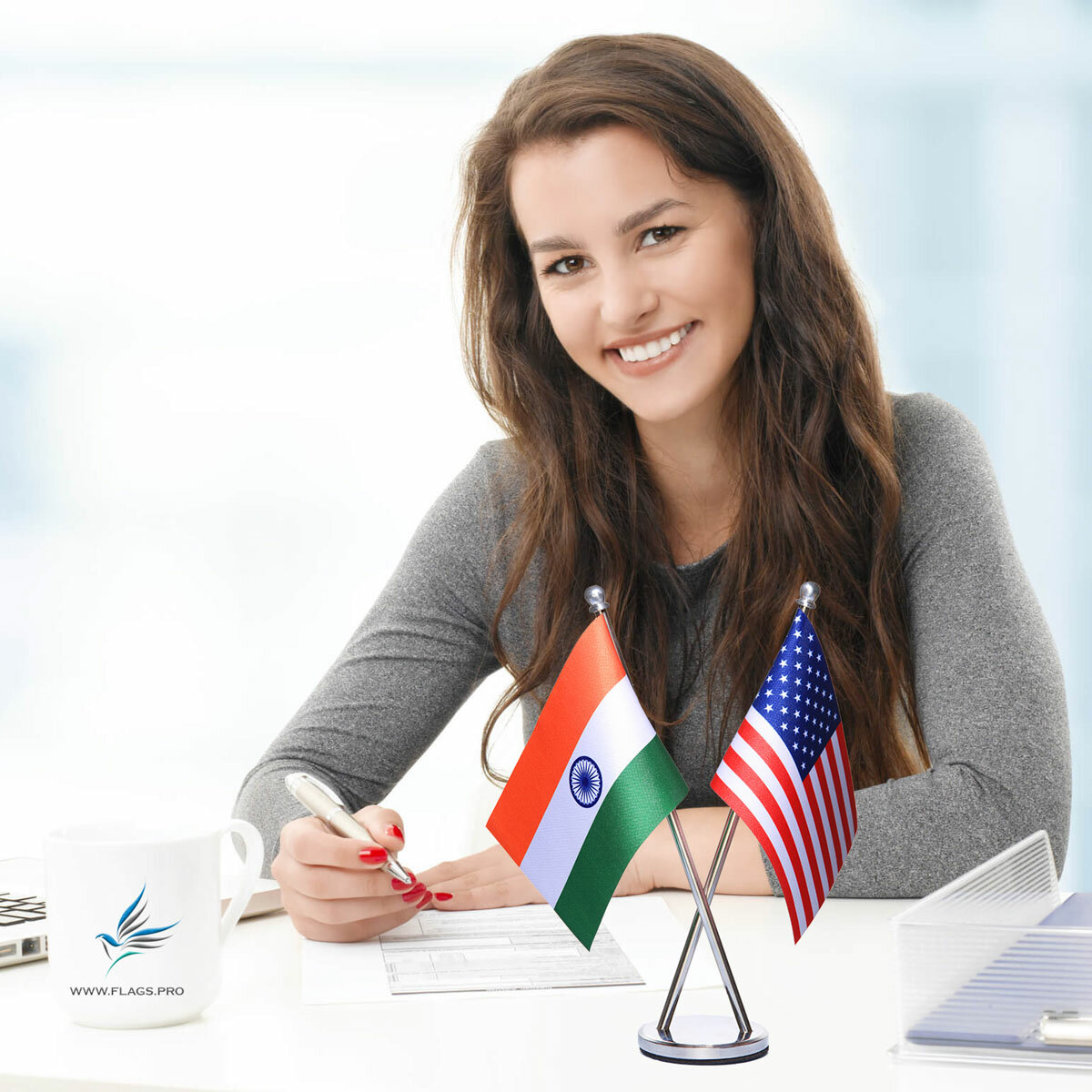 girl sitting at office desk with an indian and usa cross flag stainless steel stand