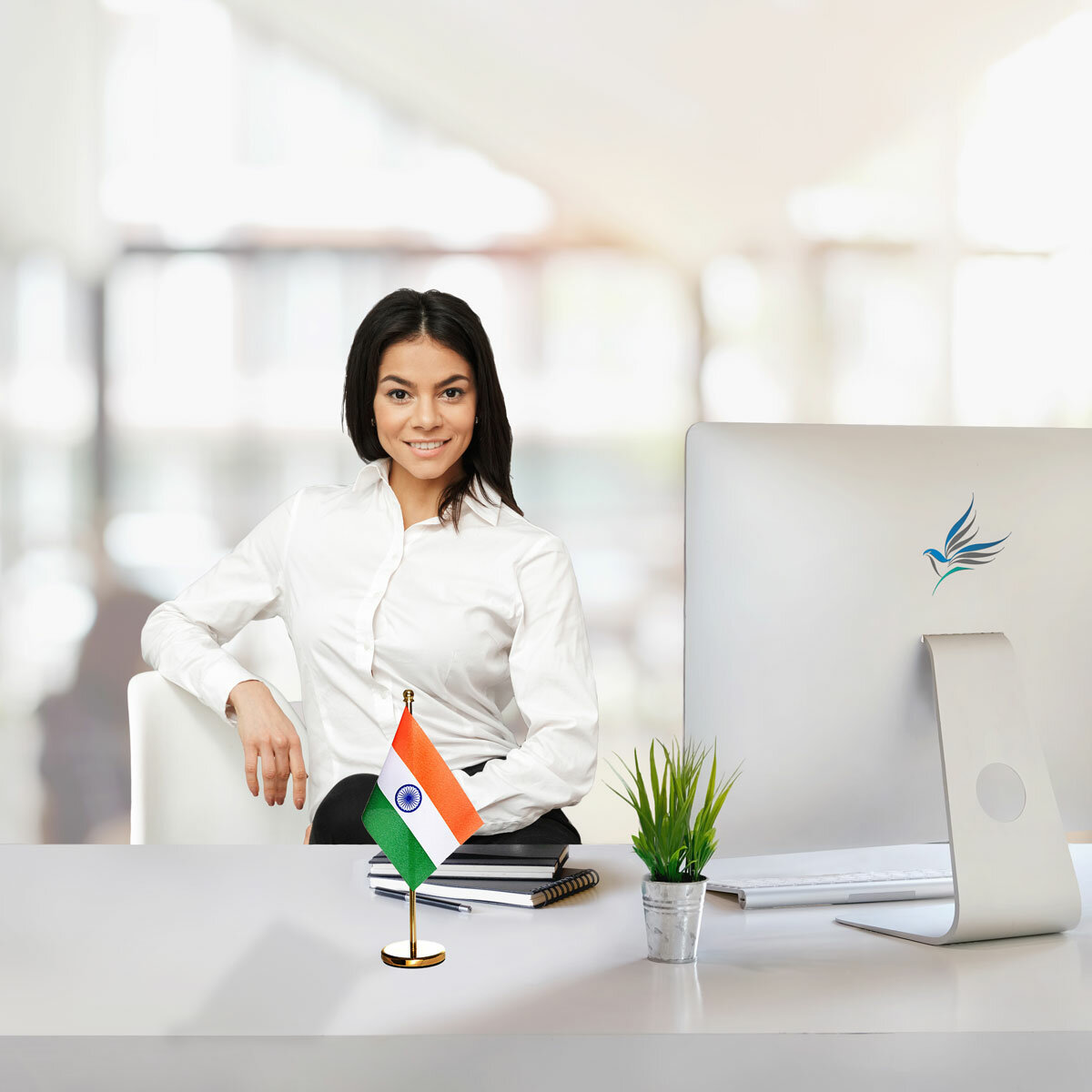 girl sitting at office desk with an indian table flag with a brass stand