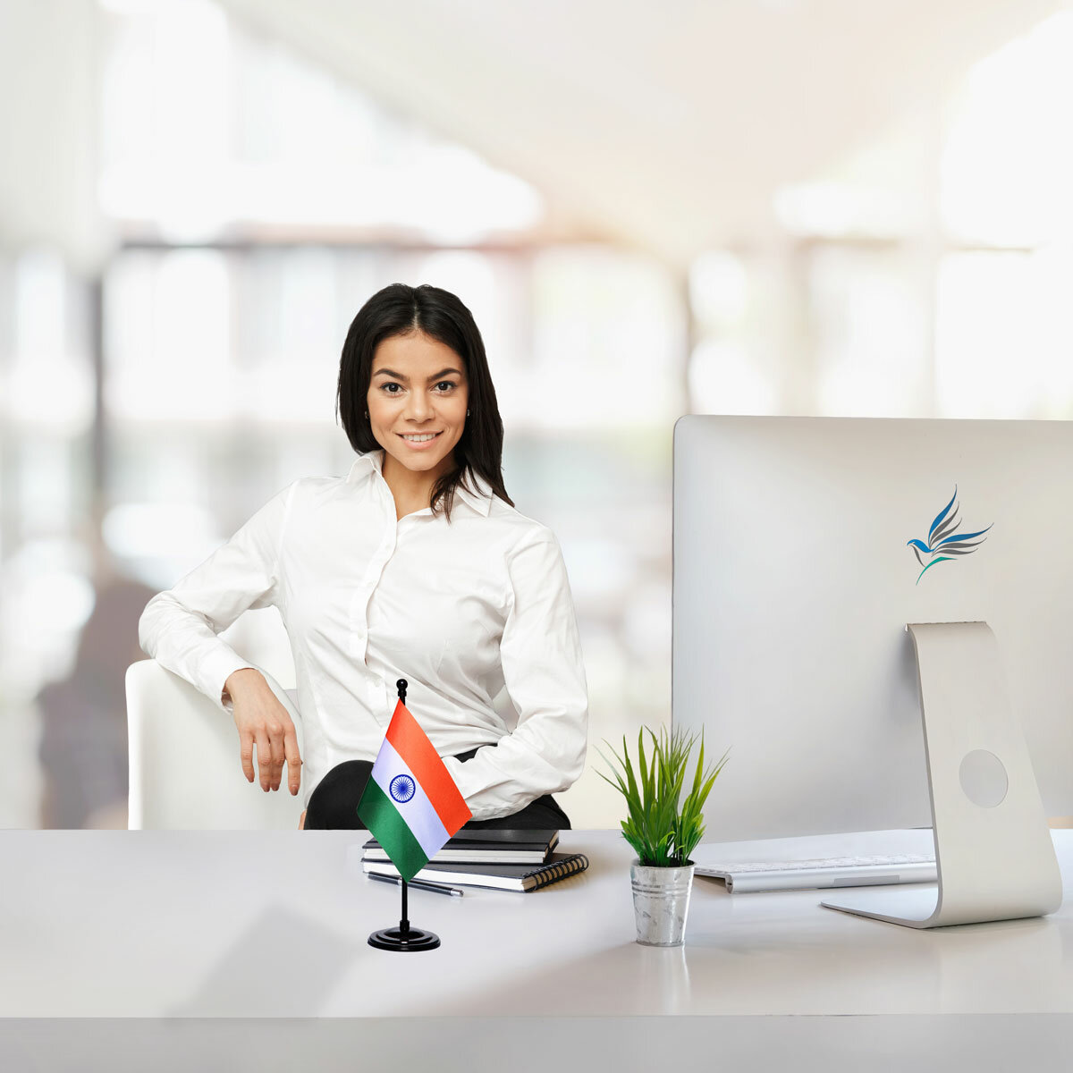 girl sitting at office desk with an indian table flag with a black plastic stand