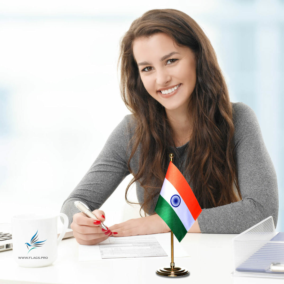 girl sitting at office desk with an indian table flag with a gold plated plastic stand
